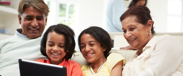 image of family viewing laptop with children